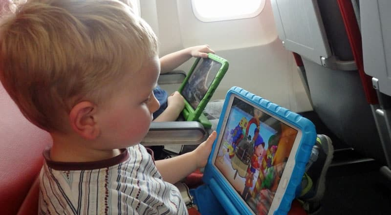 toddler using tablet while flying