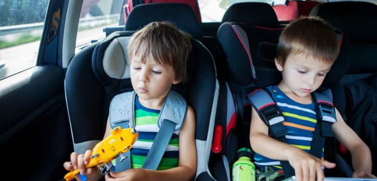 Two boy in children car seats, traveling by car and playing with toys and tablet, summertime