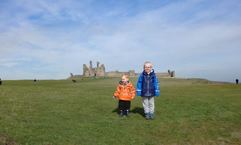 Two brothers standing in front of Dunstanburgh castle