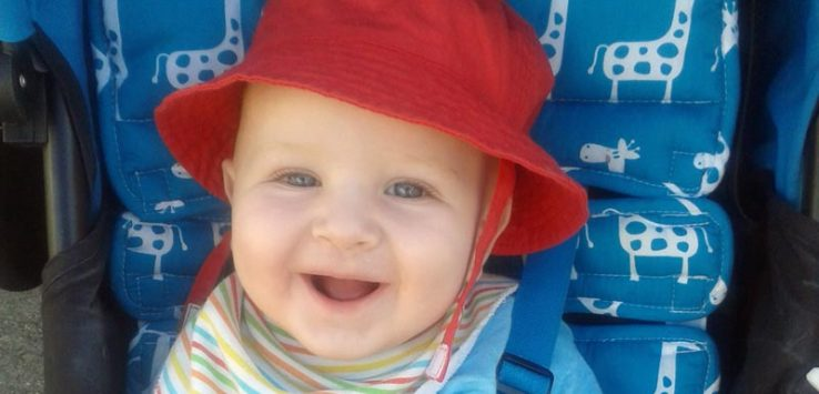 Baby wearing a red sun hat