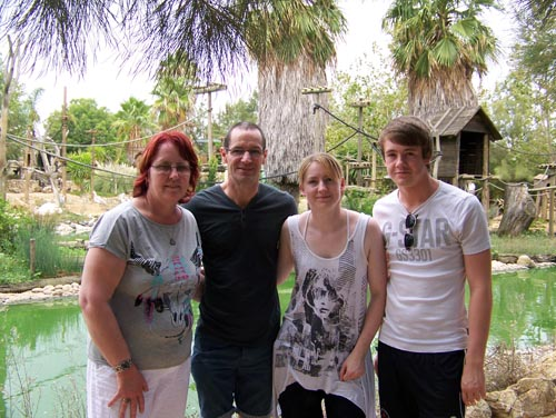 Mother, father, daughter and son posing in front of a monkey enclosure