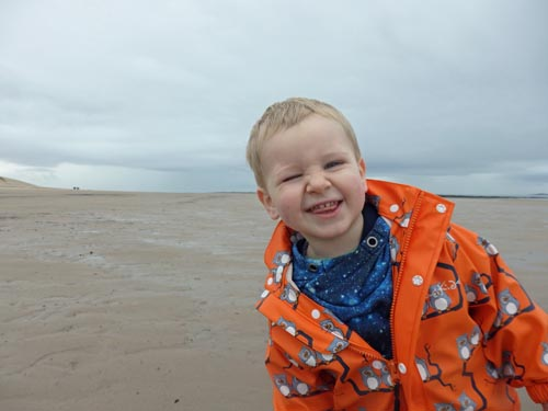 Toddler on Bamburgh Beach with a cheese smile