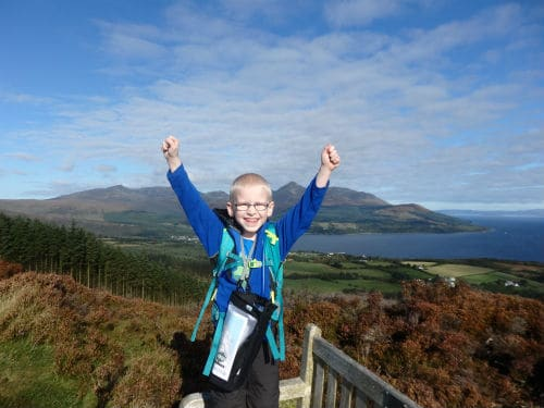 Child with arms up after climbing to top of a hill