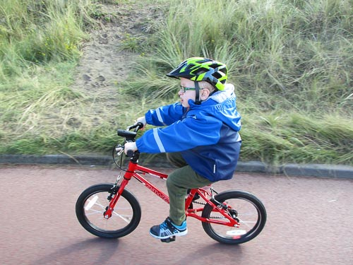 Young child cycling his red bike