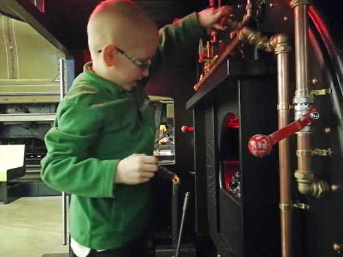 Young boy playing with the train controls