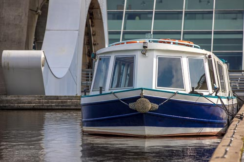 White and Blue boat moored near Falkirk Wheel, Scotland. The Falkirk Wheel is a rotating boat lift in Falkirk, Scotland, connecting the Forth and Clyde Canal with the Union Canal.
