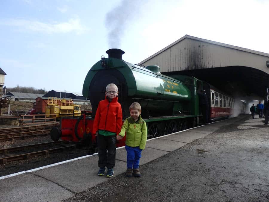 two brothers standing next to a steam train