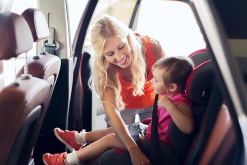 happy mother fastening child with car seat belt