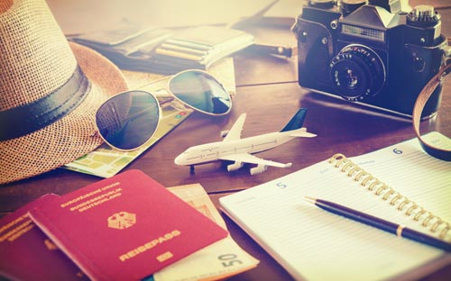 Travel planning concept. Accessories, passports, luggage, the cost of travel maps prepared for the trip on wooden table