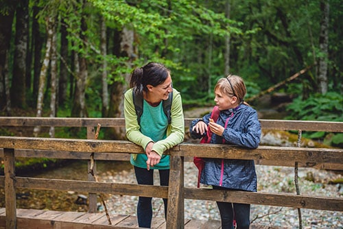 Mother and daughter with dog resting on wooden bridge in the mountain forest