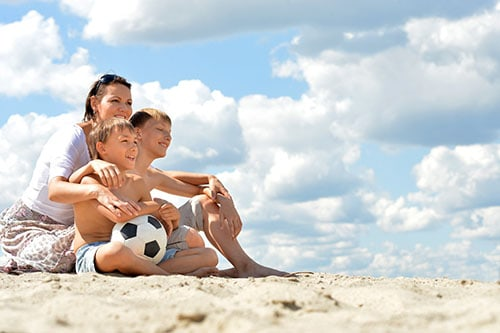 mum and sons sitting on the beach with a football