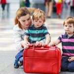 Happy family of three: Mother and two little sibling boys at the airport, traveling together.