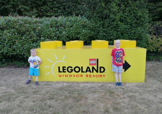 Two brothers standing at the Legoland Windsor sign
